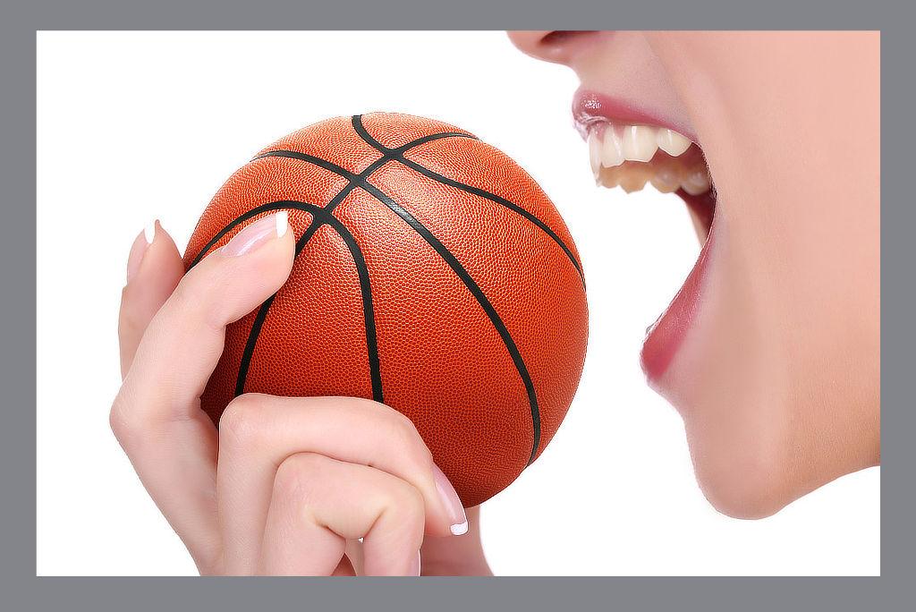 Frau beißt in einen Basketball