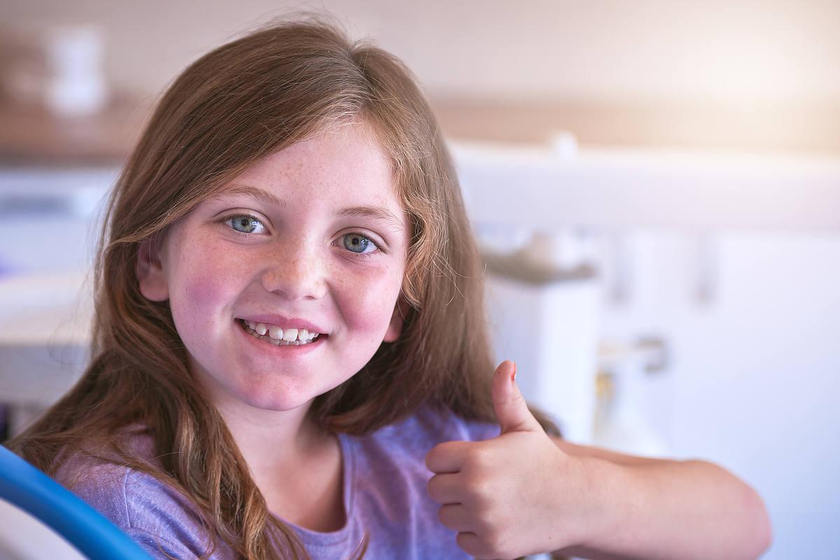Mädchen lächelt und zeigt Daumen