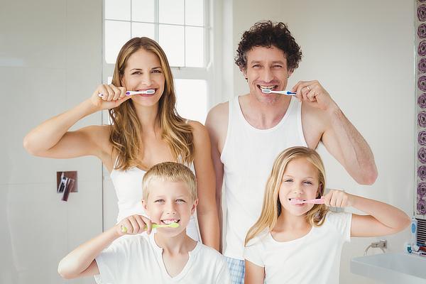 Familie putzt Zähne